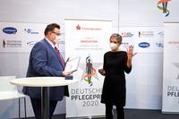 Dr. Franz Wagner, Präsident des Deutschen Pflegerats und Prof. Dr. Ingrid Darmann-Finck mit dem Deutschen Pflegepreis, der in Form eines Ringes und einer Urkunde überreicht wird